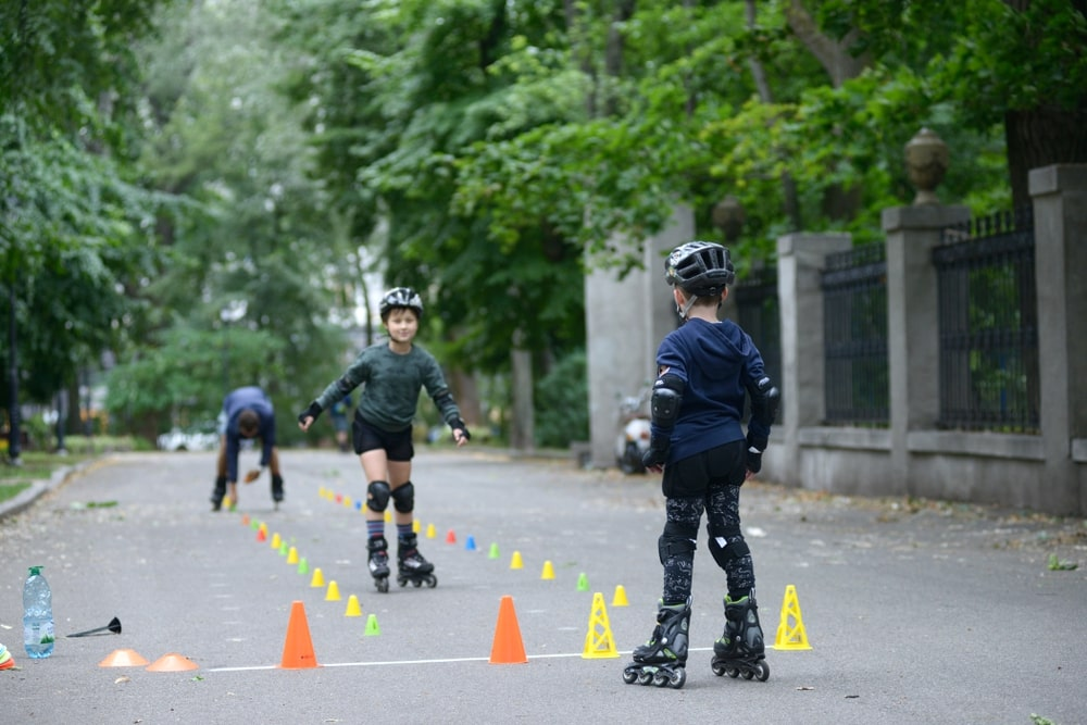 Rollerblading.Boys practicing in artistic slalom in a park